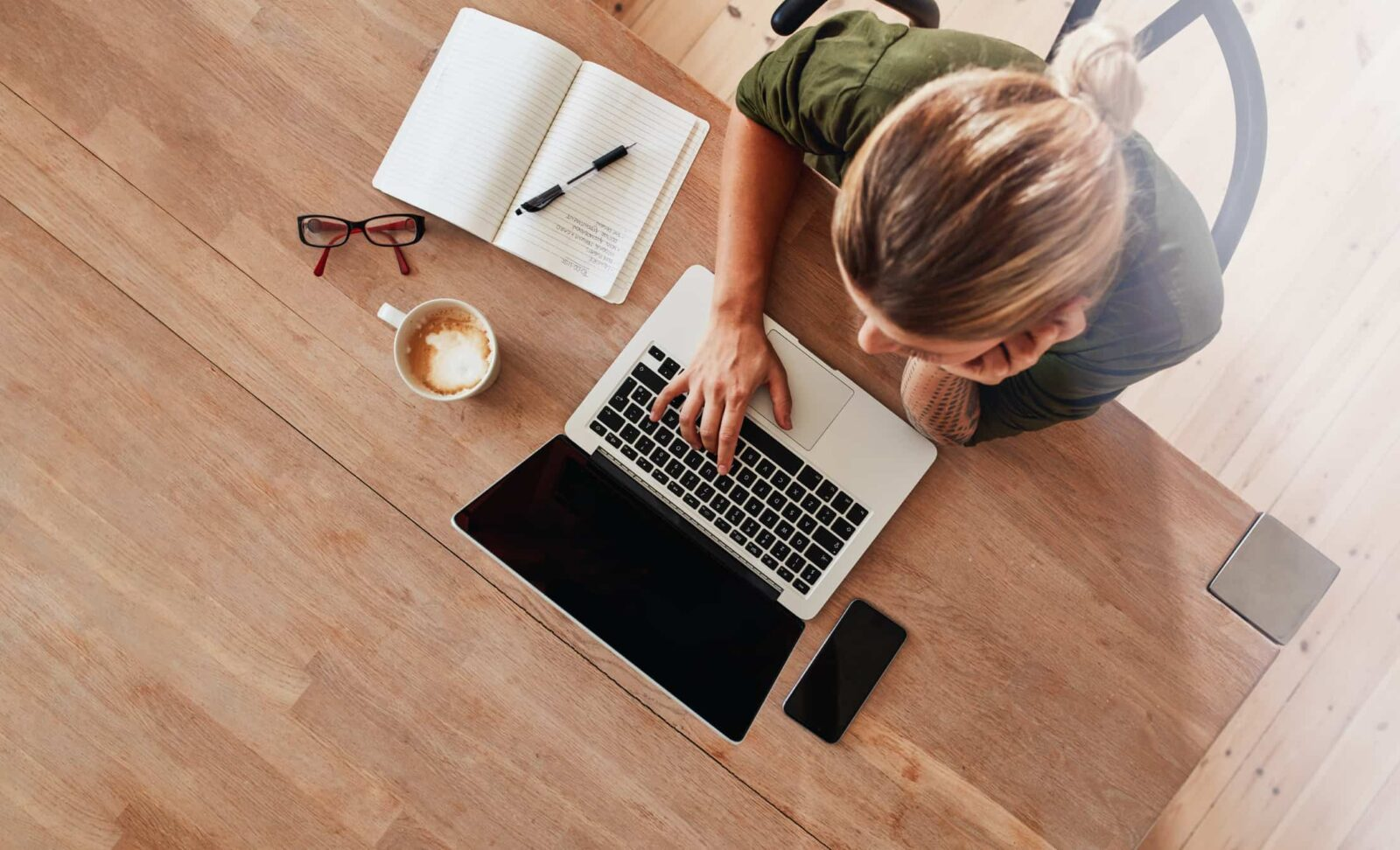 Woman creating content at a laptop.