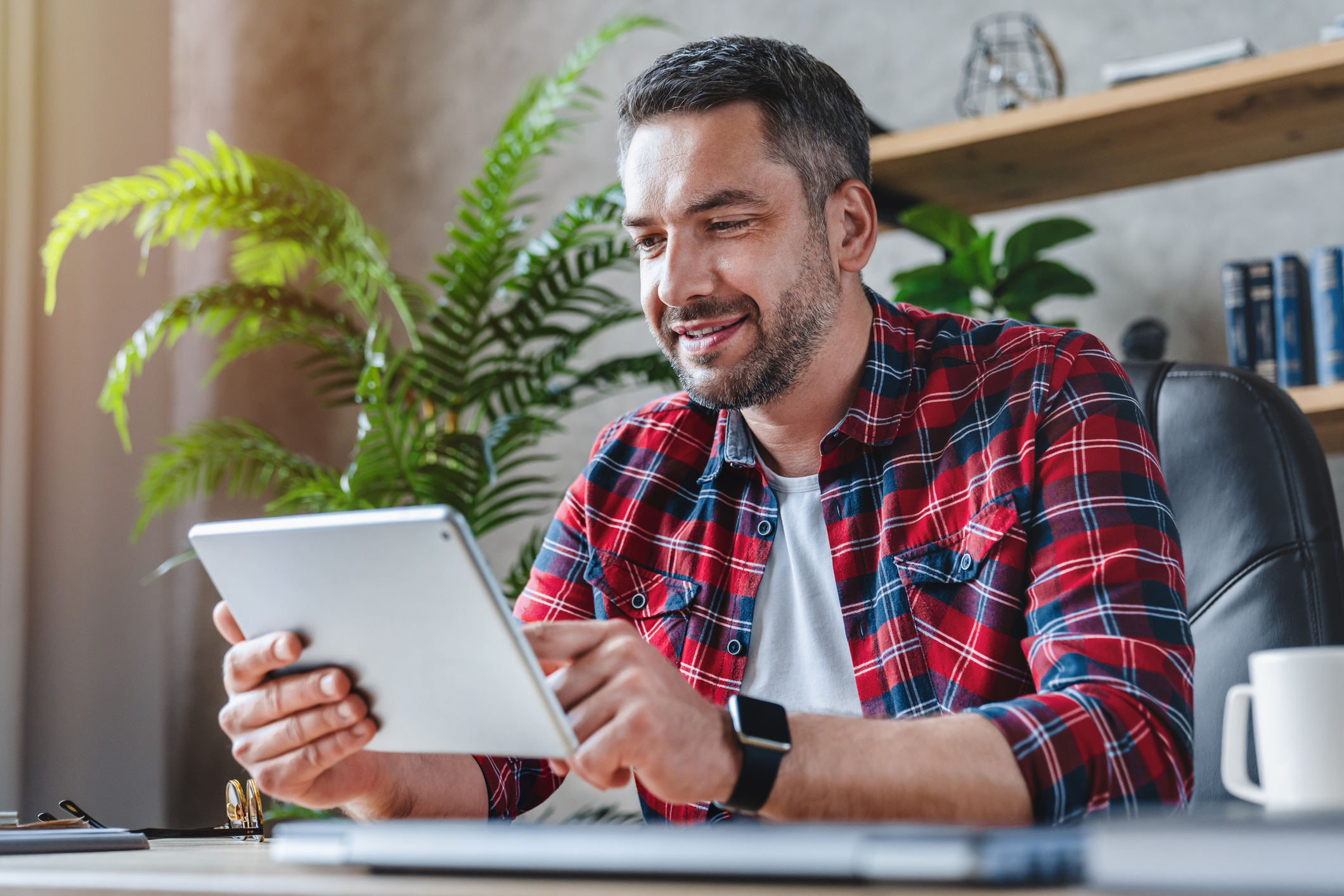 Man on tablet exploring different apps for Digital Marketing